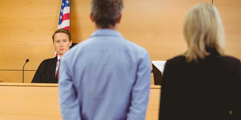 A judge in a courthouse looking at a lawyer and the defendant she's representing after he was bailed out of jail by A-Affordable Bail Bonds in Vancouver, WA