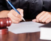 A judge signing papers in a courtroom during a hearing for a client of A-Affordable Bail Bonds, a bail bonds company in Washington State
